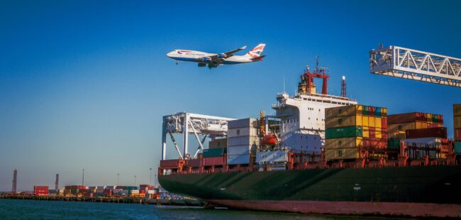 A plane comes in to land over a container ship at a port