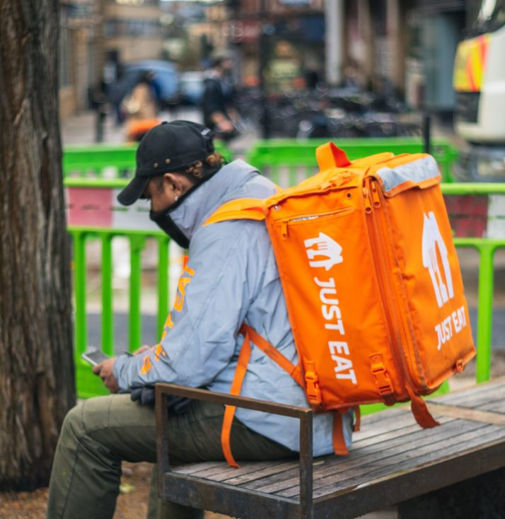 a Just Eat delivery person is a blue top with an orange bag, sits on a bench.
